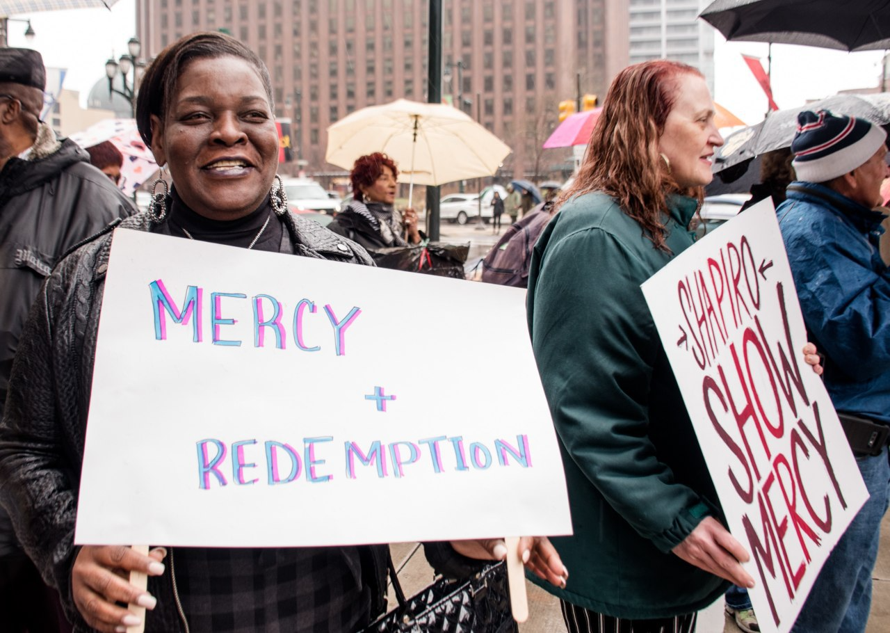 Marthea Brown holds a sign that says Mercy and Redemption
