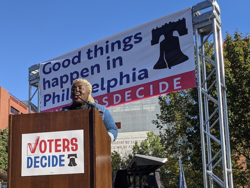 Nikki Grant stands at the podium at the Voters Decide rally