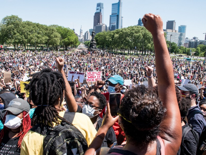 A rally of thousands of people assemble. The philly skyline is in the background and a Black person raises their fist in the foreground.
